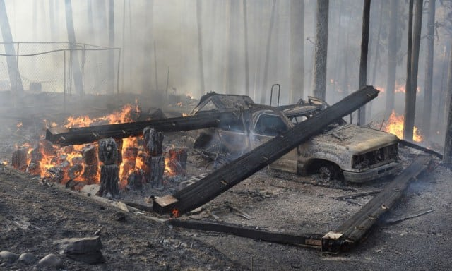 A burned truck and smoldering ruins is all that is left of a garage near a house that burned on Cedar Drive in Oakhurst,  Calif., Sunday, Sept. 14, 2014, as two raging wildfires in the state forced hundreds of people to evacuate their homes. The California Department of Forestry and Fire Protection said flames damaged or destroyed at least 21 structures. (AP Photo/The Fresno Bee, Mark Crosse)