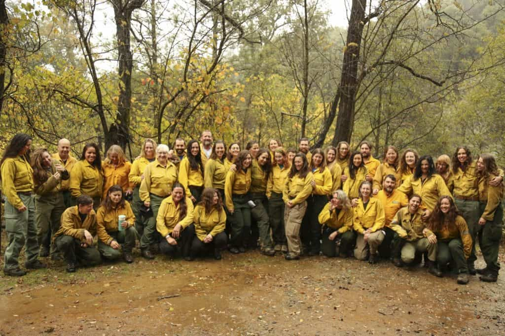 Despite the rain, participants in the first female wildfire training program gather outside to take a group photo at a Whiskeytown training camp on Oct. 27. (Tauhid Chappell/The Washington Post)