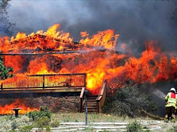 In this Saturday, June 23, 2012 photo provided by Darrell Spangler, a firefighter works the scene of a home being consumed by flames in Estes Park, Colo. (AP Photo/Darrell Spangler)